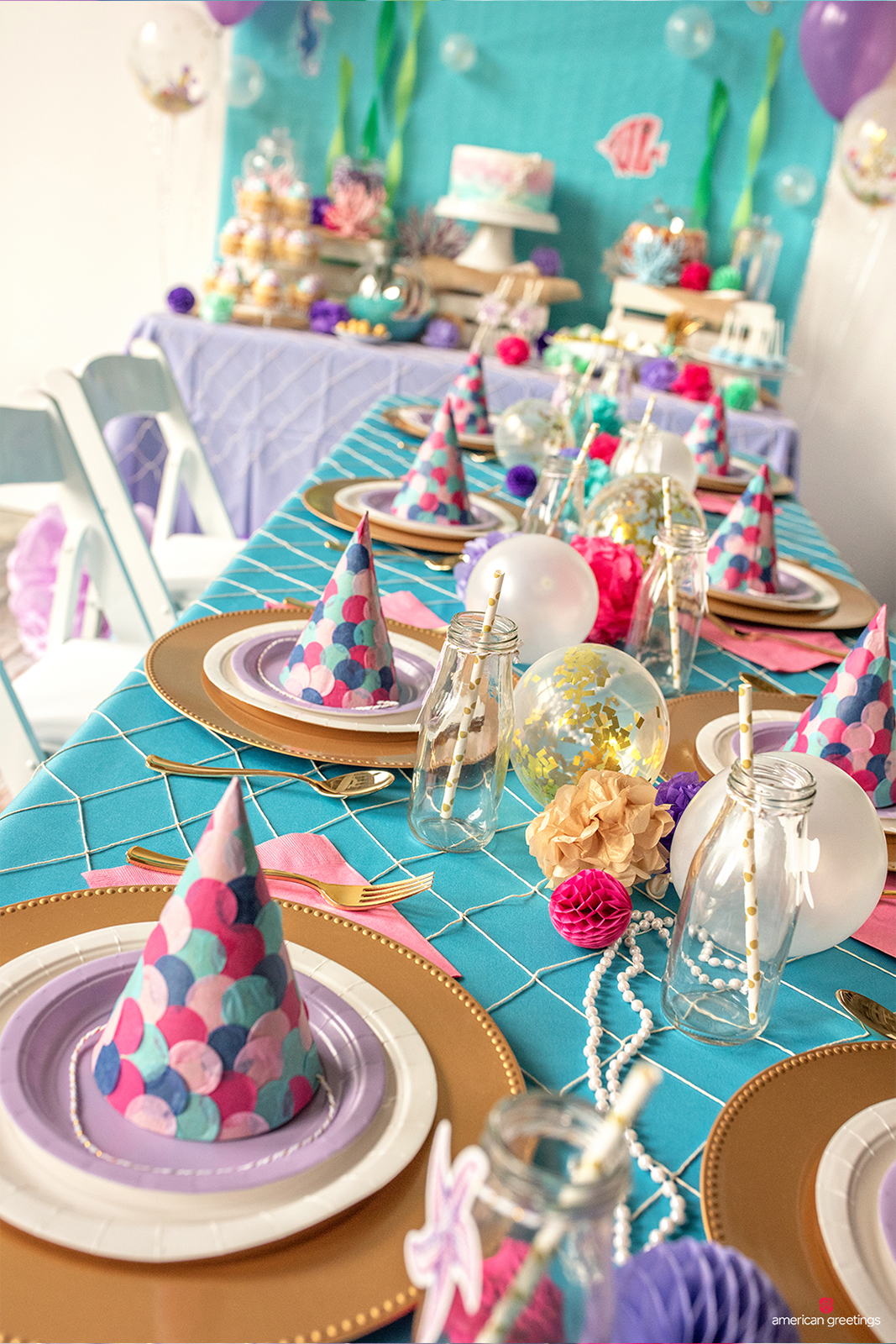 Dining table decorated with mini balloons to represent bubbles and pearls, confetti-filled balloons, pom-poms and mini honeycombs.