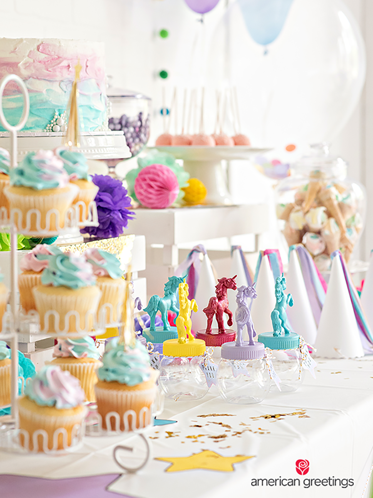 Cupcakes placed on diffrent heights and dressed up with gold tassel party picks and a lot of papper cones heads, candys, pink gumballs and a colorful cake in the midde.