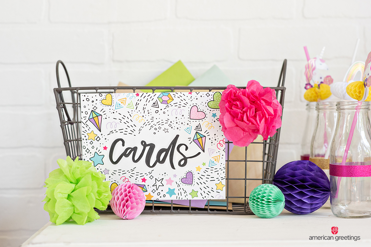 Card basket with Colorful tissue papper pom-poms and honeycombs near some guest galsses.