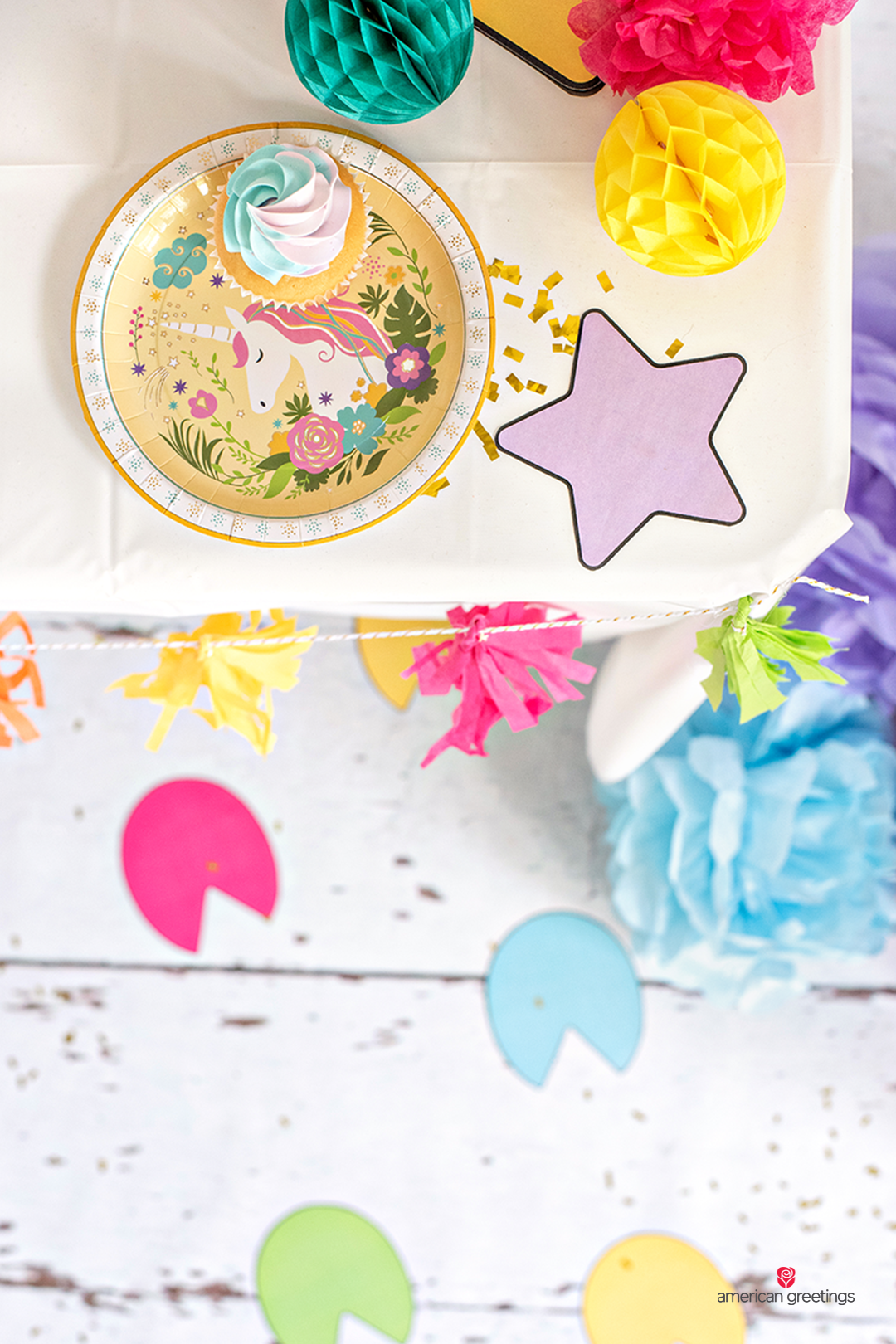 Purple printable star near a unicorn plate with a colorful cupcake on a table.