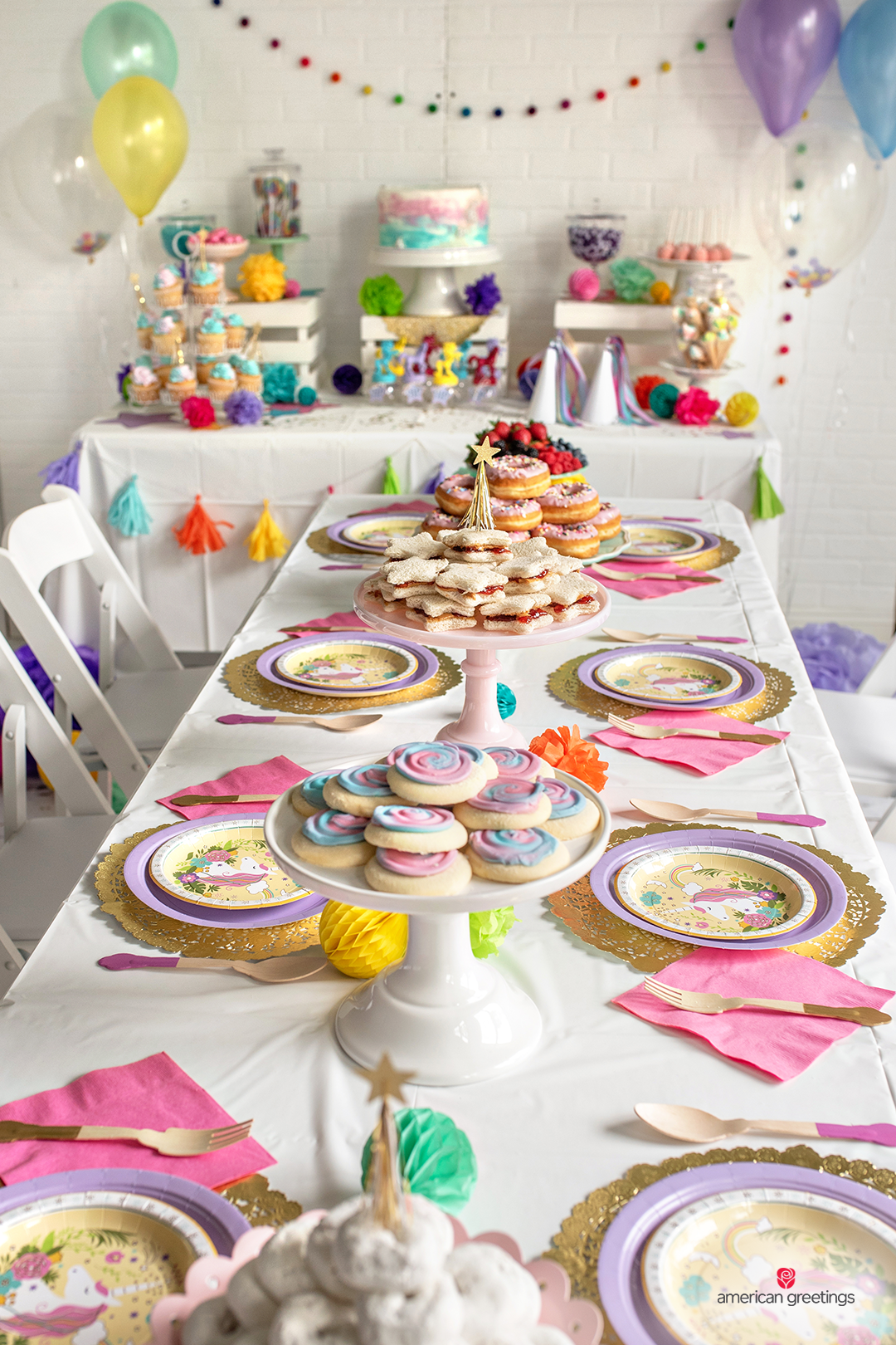 Dinner table with white tablecloth and unicorn plates, gold and pink cutllery and a lot of donuts, fruits and cakes plates.