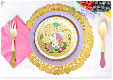 Unicorn papper plates setup with pink wook utensils and napkins.