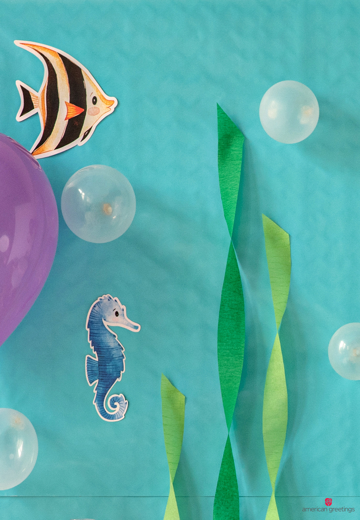 Aquatic scene created with reversible teal gift wrap, amd decorated with sea life printables, green crepe paper as sea weed, and small balloons asthe bubbles
