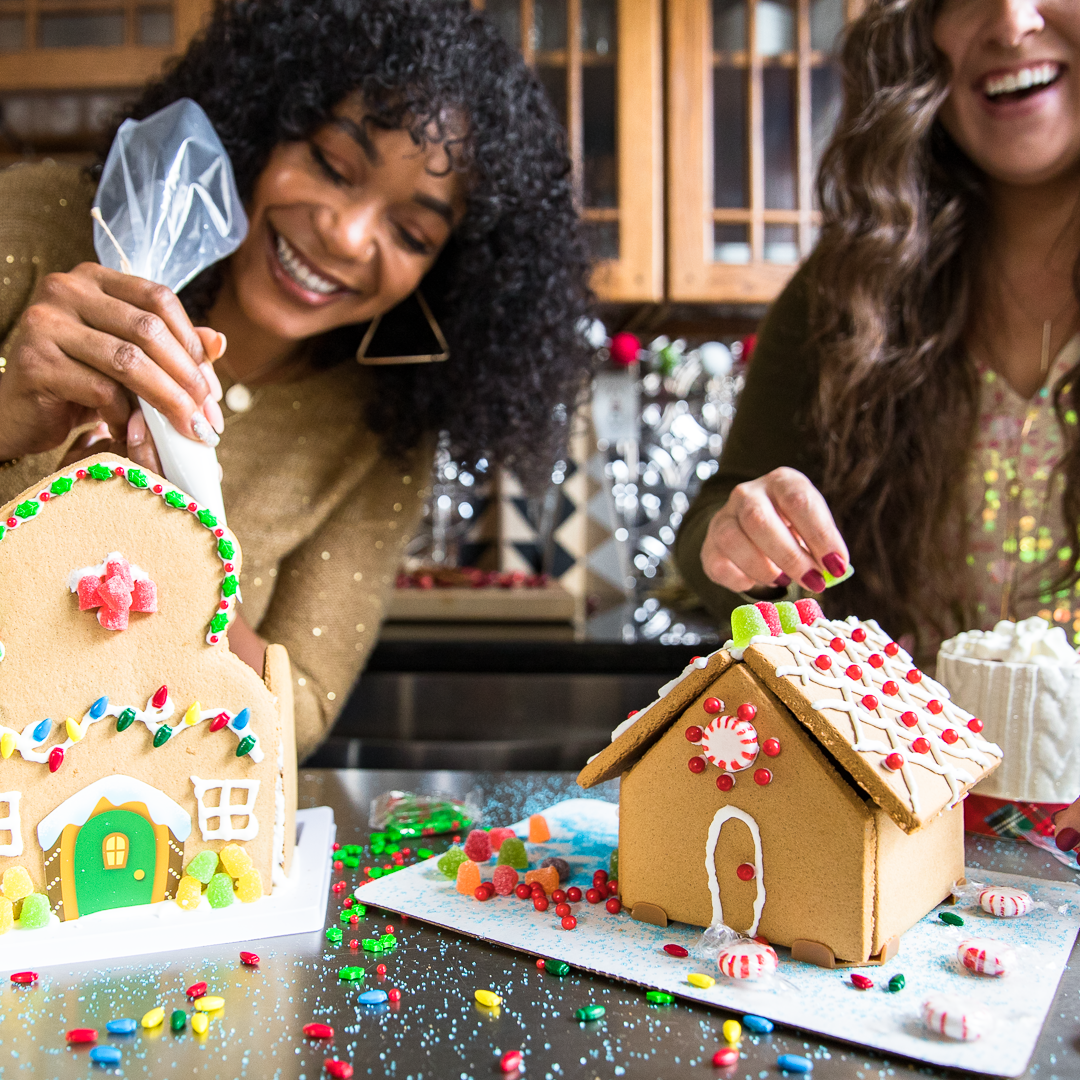 Two women having a great time making gingerbread houses together