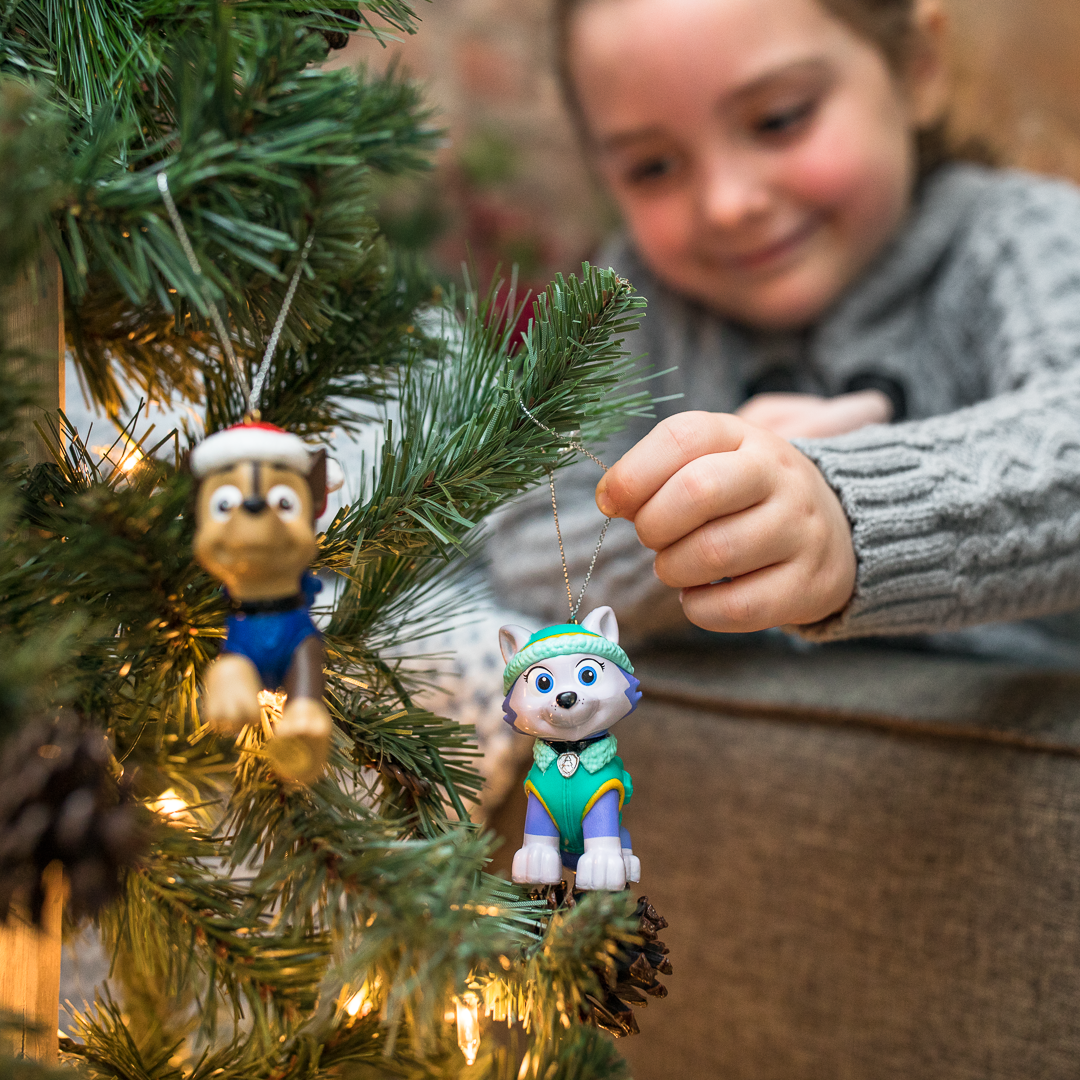 Child hanging a Christmas ornament on a tree; the ornament is of a smiling cartoon animal wearing a winter hat and jacket