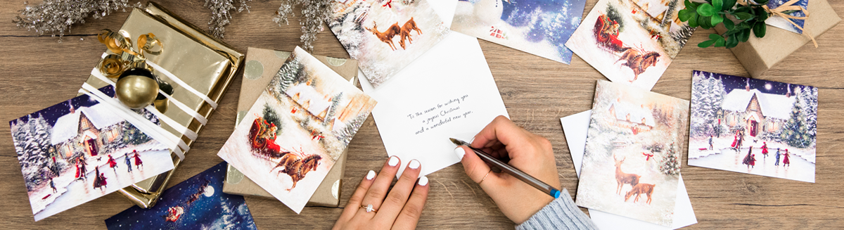 A table strewn with nostalgic Christmas cards and a few gifts, hands holding a pen and writing a message in one card.
