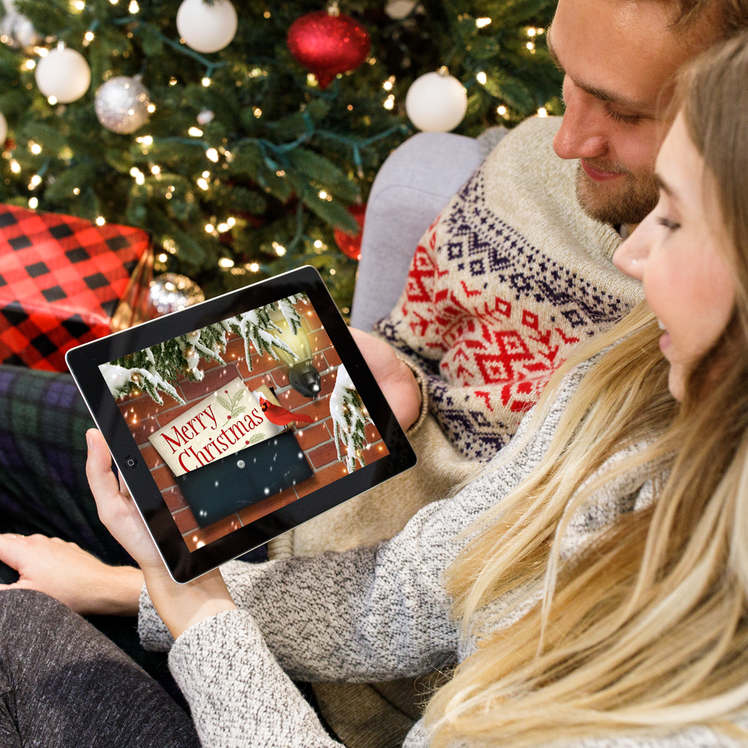 A young couple sitting in front of a Christmas tree and viewing a Merry Christmas ecard on an iPad.