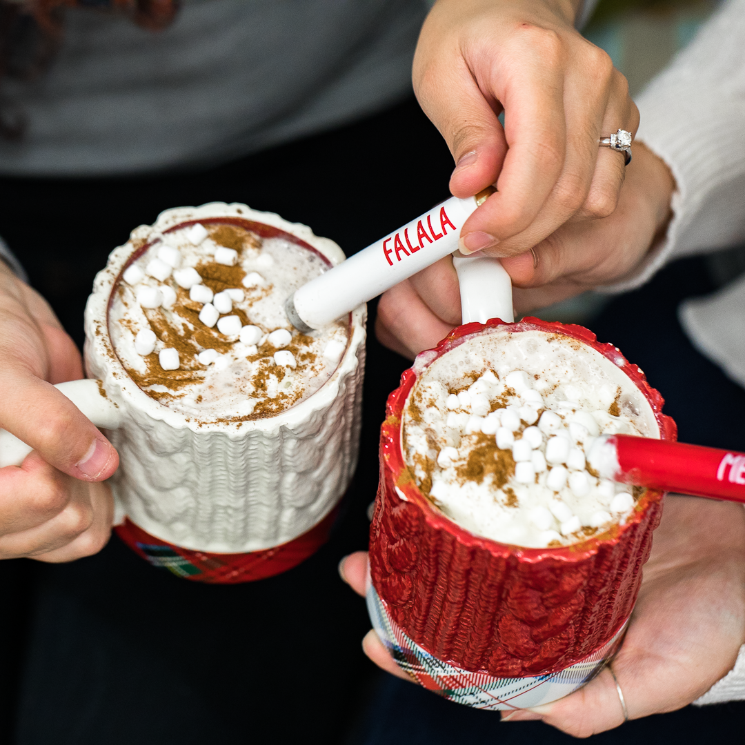 Friends having a hot chocolate drink in some red and white Christmas mugs.