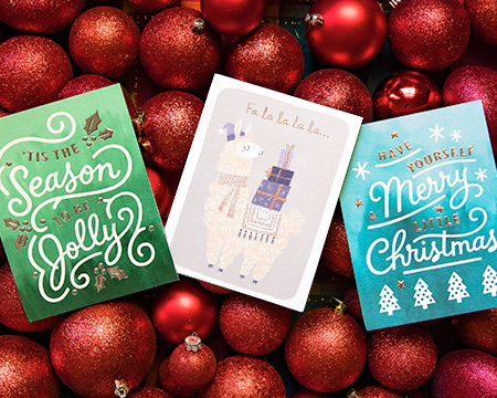 Three Christmas greeting cards sitting on a collection of sparkly red ornaments