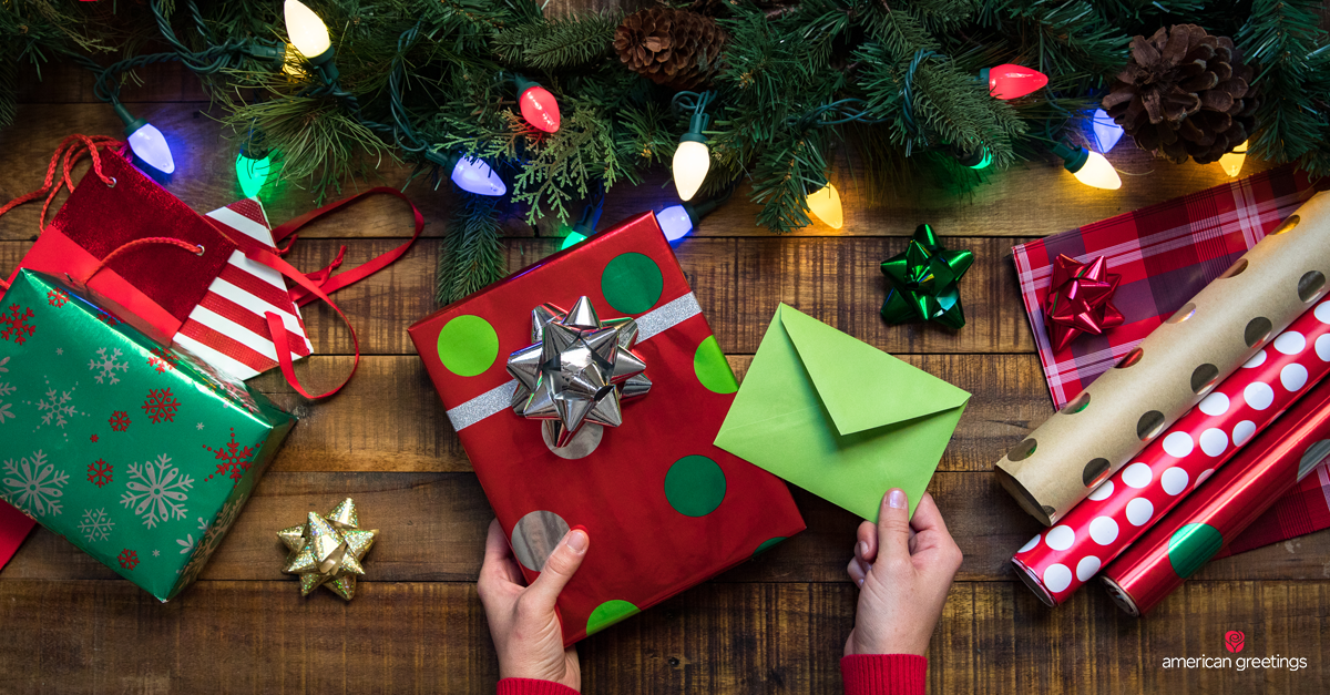 Hands holding a wrapped Christmas gift and card envelope, with bows, wrapping paper and gift bags nearby on a table.