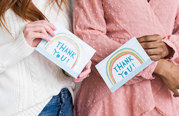 Two girls holding rainbow thank you stationery set