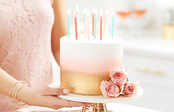 Girl holding pink and gold cake with candles