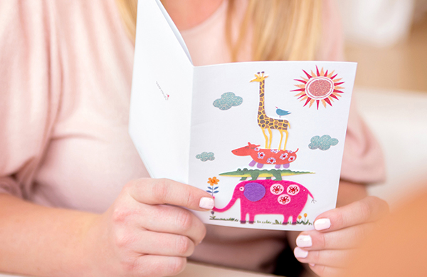 Girl holding baby greeting card with a giraffe, hippo and elephant