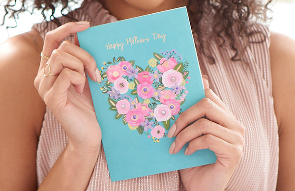 woman holding floral heart mother's day card