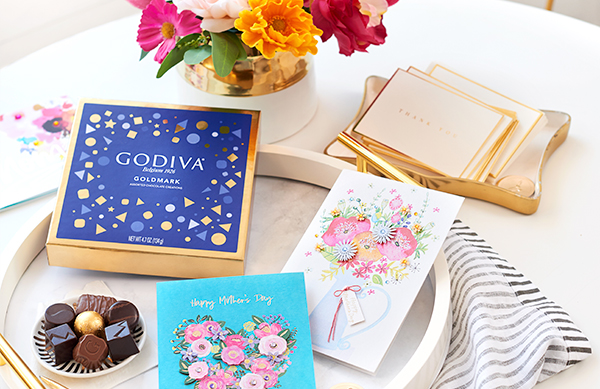 A tray of floral mother's day cards and chocolates