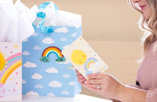 woman holding baby greeting card in front of gift bags